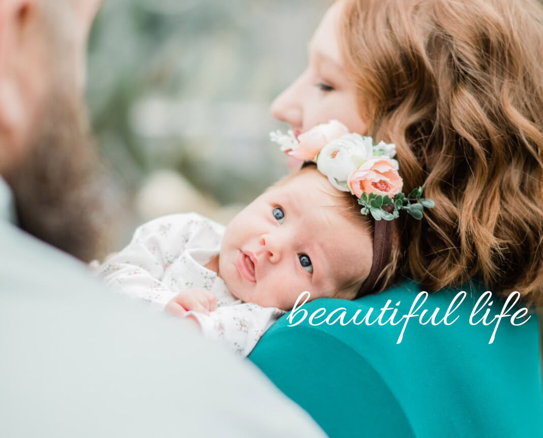 Parents holding baby with phrase Beautiful Life